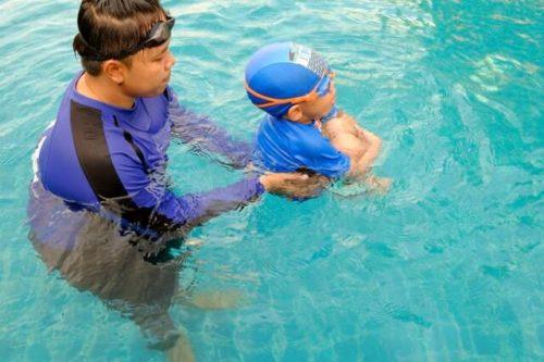 水泳教室の先生と子ども